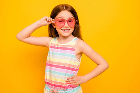 Portrait of cute child touching specs isolated over yellow background