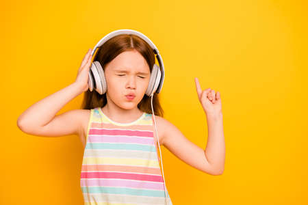 Portrait of charming kid wearing tank-top singlet with closed eyes listening music isolated over yellow background Stock Photo