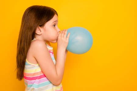 Profile side photo of charming kid inflating baloon isolated over yellow background