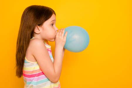Profilseitenfoto des charmanten Kindes, das Ballon aufbläst, isoliert über gelbem Hintergrund Standard-Bild