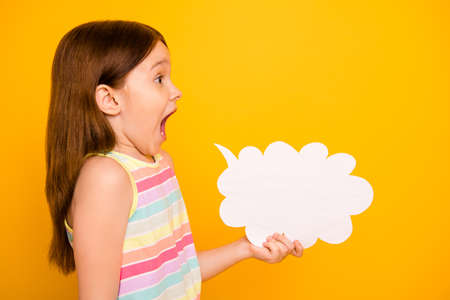 Profile side photo of cute child holding paper card bubble shouting yelling isolated over yellow background Stock Photo