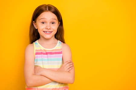 Portrait of cute kid with crossed hands looking wearing tank-top isolated over yellow background