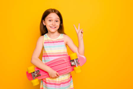 Portait of cute lovely child holding skate board looking isolated over yellow background