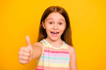 Portrait of charming cute kid raising thumb up screaming shouting wearing colorful singlet isolated over yellow background