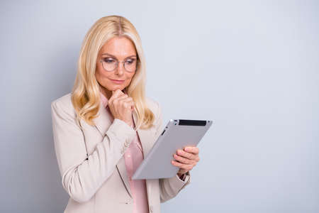 Portrait of  nice-looking attractive lovely stylish focused concentrated peaceful wavy-haired lady holding in hands e-book reading news isolated over light white gray pastel background