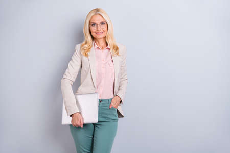 Portrait of  nice attractive stylish cheerful cheery candid wavy-haired lady expert shark specialist carrying in hands laptop isolated over light white gray pastel background