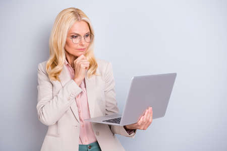Portrait of nice attractive stylish minded serious focused concentrated wavy-haired lady holding in hands laptop e-commerce isolated over light white gray pastel background