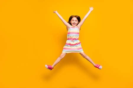 Full size photo of pretty child jumping raising hands isolated over yellow background