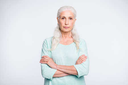 Portrait of focused retiree with crossed arms looking wearing turquoise sweater isolated over white background 스톡 콘텐츠