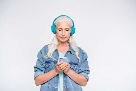 Portrait of serious old retiree holding gadget look listen soundtracks isolated over white background