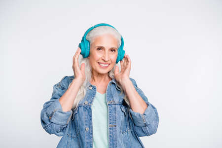 Portrait of lovely old lady touch headset listen soundtrack isolated over white background