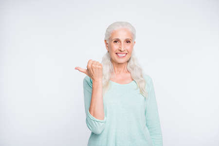 Portrait of confident person showing advertisement with her thumb wearing turquoise jumper isolated over white background