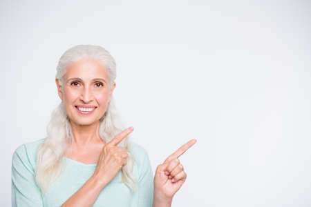 Close up photo of charming lady pointing in copy space looking wearing turquoise jumper isolated over white background