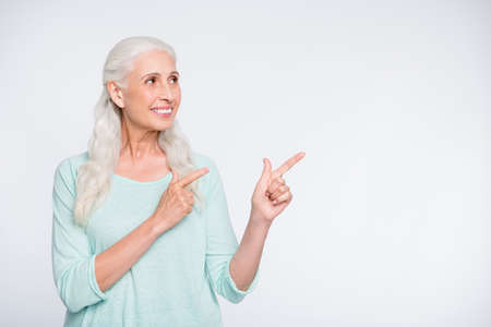 Portrait of charming lady pointing perfect adverts wearing turquoise sweater isolated over white background