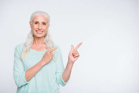 Portrait of attractive lady pointing promotion with her index finger wearing teal jumper isolated over white background