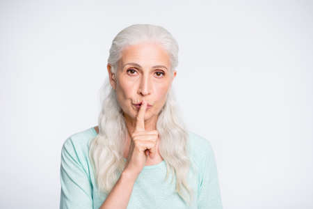 Close up photo of tricky old woman placing her index finger near face say hush wearing teal sweater isolated over white background Imagens