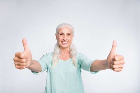 Portrait of cheerful lady showing thumb-up smiling advertising wearing teal pullover isolated over white background