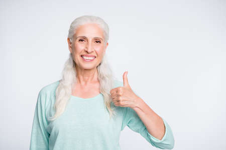 Portrait of nice retiree showing thumb up recommending promo wearing turquoise pullover isolated over white background