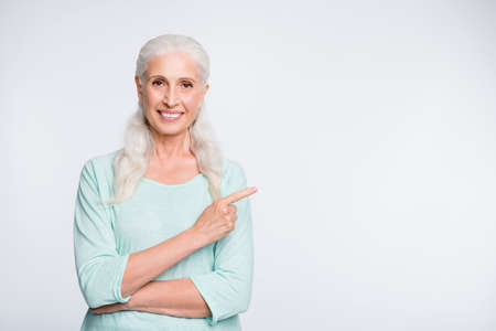 Portrait of charming old woman pointing at copy space showing ads promo wearing teal jumper isolated over white background