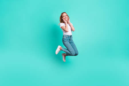 Full length photo of cute youngster touching her face with palms isolated over teal turquoise background 写真素材