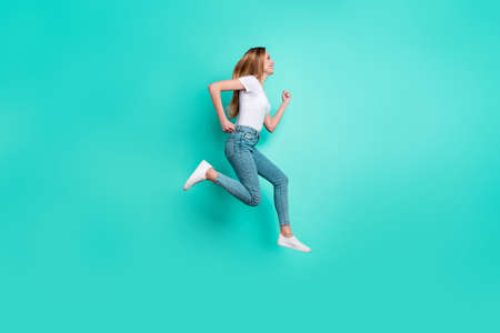 Profile side full size photo of nice girl running smiling isolated over teal turquoise background