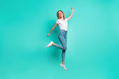 Full size photo of pretty lady raising hand arms smiling isolated over teal turquoise background