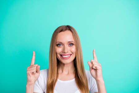 Nahaufnahme eines charmanten Promoters, der mit dem Finger nach oben zeigt und lächelnd ein weißes T-Shirt trägt, das über türkisfarbenem Hintergrund isoliert ist? Standard-Bild