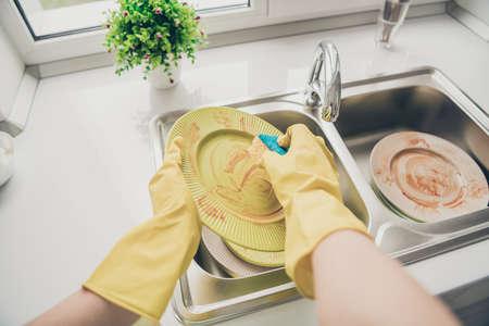 Vista de primer plano recortada de ella con guantes de goma haciendo que el servicio de limpieza sea una zona de confort acogedora pulido fregado en una cocina interior blanca clara en el interior