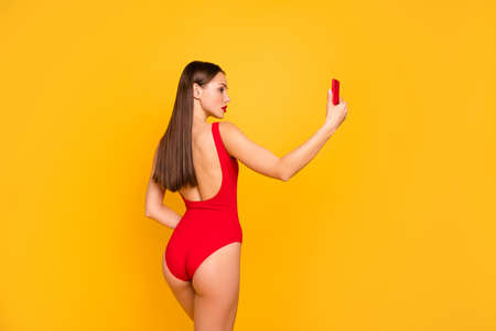 Rear back behind view of nice-looking attractive glamorous gorgeous lovely fascinating sportive straight-haired lady perfect figure making selfie isolated on bright vivid shine yellow background