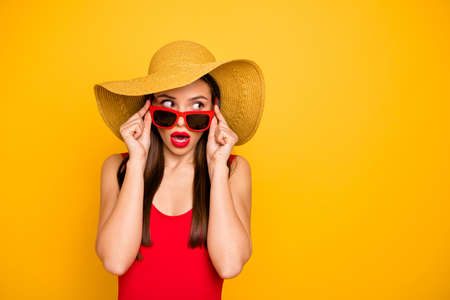 Photo of amazing lady nice look came seaside trip voyage listen hotel neighbors fight sly person wear specs sun hat red swimming suit isolated yellow background