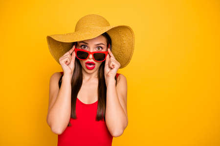 Photo of amazing lady bright lipstick nice colorful look came seaside trip voyage staring cold water ocean oh no wear specs sun hat red swimming suit isolated yellow background
