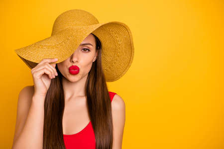 Close-up portrait of her she nice attractive glamorous lovely posh calm peaceful straight-haired lady hiding eye behind hat sending sweet kiss isolated on bright vivid shine yellow background