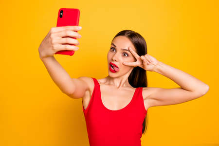 Portrait of her she nice attractive glamorous gorgeous lovely coquettish posh crazy straight-haired lady taking selfie showing v-sign having fun isolated on bright vivid shine yellow background Фото со стока