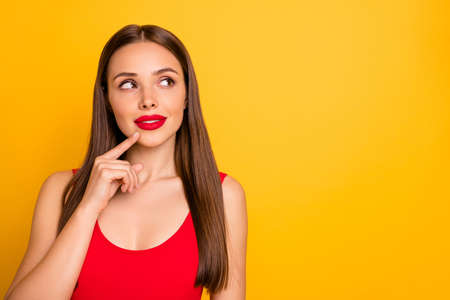Close-up portrait of her she nice-looking attractive lovely adorable charming cute winsome straight-haired lady looking aside thinking touching chin isolated over bright vivid shine yellow background