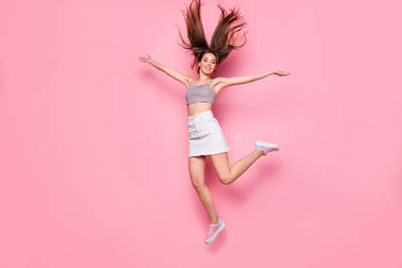 Portrait of pretty youth in white skirt gray singlet raising hands isolated over pink background