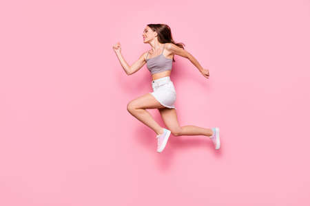 Profile side full body photo of pretty girl running wearing gray tank-top white skirt isolated over pink background