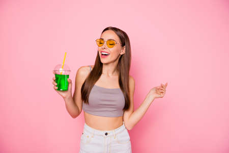 Portrait of lovely charming lady holding plastic cup closing eyes enjoying wearing grey tank-top white short isolated over pink background Stock Photo