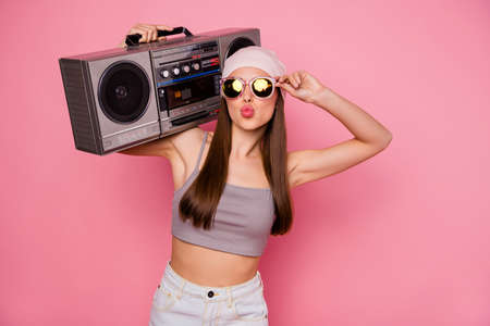 Portrait of stylish trendy person holding boombox sending air kisses wearing eyeglasses eyewear isolated over pink background Reklamní fotografie