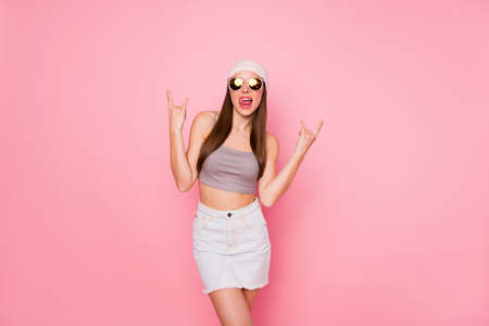 Portrait of funny teenager making rock-and-roll signs wearing eyewear eyeglasses tank-top isolated over pink background