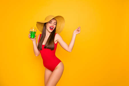 Photo of beautiful amazing lady nice colorful look green alcohol beverage chill entertainment wear sun hat red swimming suit isolated yellow background