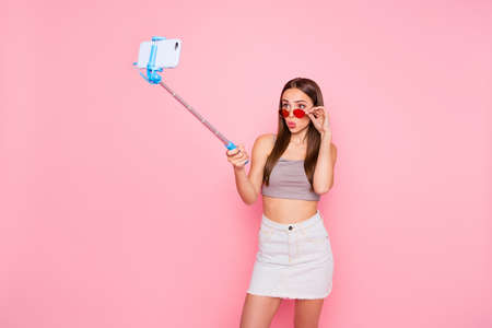 Portrait of pretty youth having monopod with modern technology making photo wearing tank-top singlet isolated over pink background Stock Photo