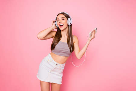 Portrait of cute youth holding device closing eyes hearing playlist wearing trendy stylish tank-top denim jeans skirt isolated over pink background