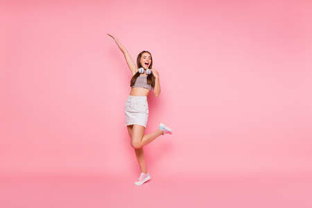 Full size photo of carefree lady with close eyes raising hand leg wearing white denim jeans skirt grey tank-top isolated over pink background