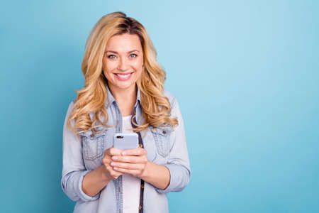 Portrait of cheerful charming lady with toothy smile holding modern technology looking at camera isolated over blue background