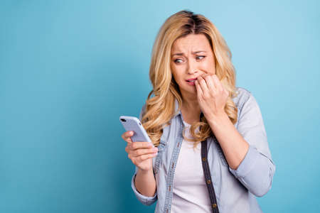 Portrait of disappointed beautiful lady biting her fingers looking at device screen isolated over blue background Standard-Bild