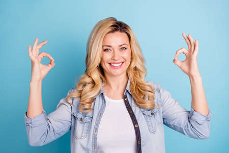 Close up photo of pretty charming lady making okay sign with her fingers isolated over blue background