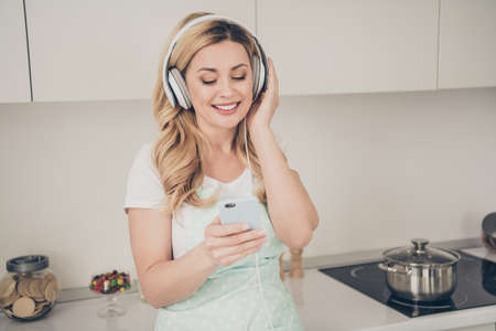 Portrait of her she nice attractive lovely charming cheerful cheery dreamy wavy-haired lady maid having fun free time track list mp3 audio meloman in light white interior kitchen