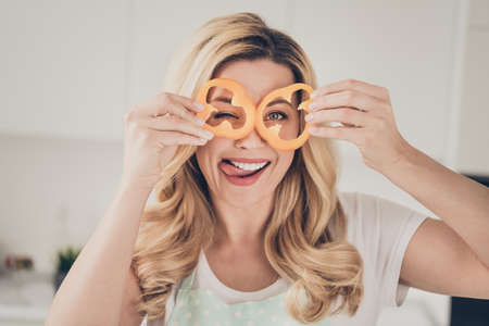 Close-up portrait of her she nice attractive lovely playful careless cheerful cheery wavy-haired lady having fun with orange pepper slices pieces in light white interior kitchen indoors 写真素材