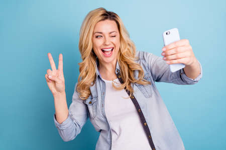 Portrait of cheerful woman video calling holding device making photos v-signs isolated over blue background