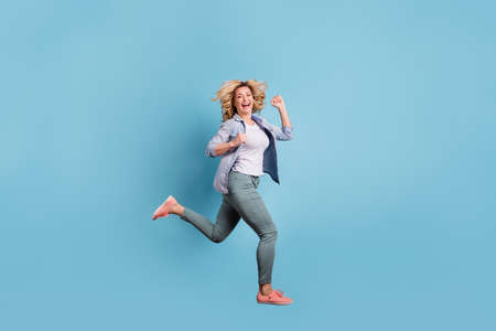 Full size profile side photo of nice lady running laughing wearing pants trousers isolate dover blue background